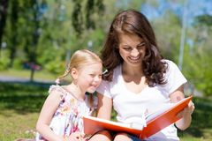 Girl and a young woman reading a book together Royalty Free Stock Images