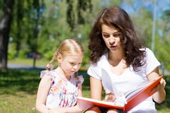 Girl and a young woman reading a book together Stock Images