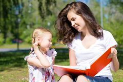 Girl and a young woman reading a book together Royalty Free Stock Photos