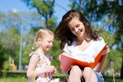 Girl and a young woman reading a book together Royalty Free Stock Photo