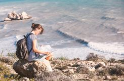 Girl young woman traveler with a backpack and map in hand walks. On the background of a beautiful landscape, the sea and the hills Royalty Free Stock Photos