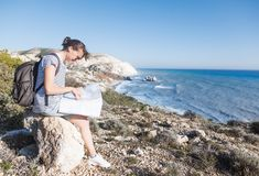 Girl young woman traveler with a backpack and map in hand walks. On the background of a beautiful landscape, the sea and the hills Royalty Free Stock Images