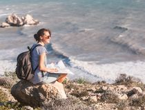 Girl young woman traveler with a backpack and map in hand walks. On the background of a beautiful landscape, the sea and the hills Stock Images