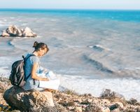 Girl young woman traveler with a backpack and map in hand walks. On the background of a beautiful landscape, the sea and the hills Royalty Free Stock Photo