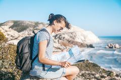 Girl young woman traveler with a backpack and map in hand walks. On the background of a beautiful landscape, the sea and the hills Stock Photo