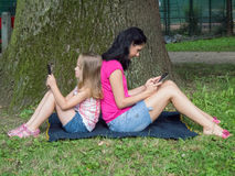 Girl and young woman using tablet Royalty Free Stock Image