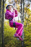 Girl on Zip Line. Young girl on zip line between trees in an adventure park royalty free stock images