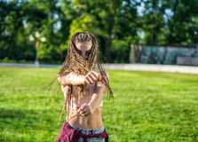 Girl with zizi cornrows dreadlocks dancing on lawn Stock Photo