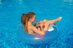 Girl with zizi cornrows dreadlocks lying in swimming circle Stock Photo