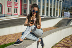 Girl with zizi cornrows dreads chatting on her smartphone Stock Photos