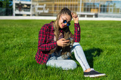 Girl with zizi cornrows dreads chatting on her smartphone Stock Images