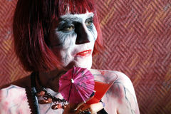 Girl with zombie makeup with glass of red cocktail. On red wall royalty free stock image