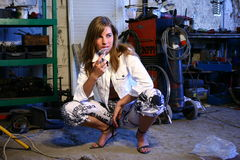 Girl1. Hard working girl at work in a garage.Thinking Royalty Free Stock Image
