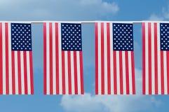 Girland av USA-flaggor mot himlen med moln arkivfoto