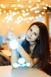 Girland för jul för kvinnainnehav glödande i händer arkivfoton