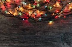 Girland med kulöra ljus på en träbakgrund vita röda stjärnor för abstrakt för bakgrundsjul mörk för garnering modell för design Arkivbild