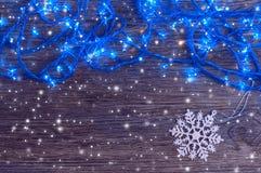 Girlande mit Blaulichtern und einer weißen Schneeflocke auf einem hölzernen Hintergrund Weihnachts- und des neuen Jahreshintergru Lizenzfreie Stockbilder