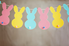 Girlande mit bunten Papierkaninchen auf grauem Hintergrund Konzept Ostern Bunny Banner Stockbilder