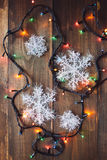 Girlande und Schneeflocken auf dem Holztisch Lizenzfreies Stockbild