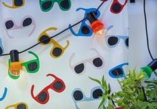 Girlande von mehrfarbigen elektrischen Birnen auf dem Hintergrund des hellen Gewebes lizenzfreie stockfotografie