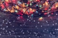 Girlanden med kulöra ljus på en träbakgrund dekoreras med flygsnö vita röda stjärnor för abstrakt för bakgrundsjul mörk för garne Fotografering för Bildbyråer