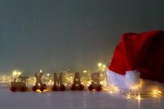girlanden tänder bredvid den santa hatten och träbokstäver Royaltyfri Foto