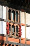 Girlander av röda peppar hängs på ett fönster (Bhutan) royaltyfri foto