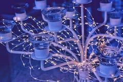 Girlandljus runt om en lyxig exponeringsglasljusstake, en festlig afton, blå bakgrund, glödande varma ljus royaltyfri foto