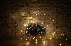 Girlandljus runt om vasen för exponeringsglasspegel på beigastenbakgrund I darken arkivfoto