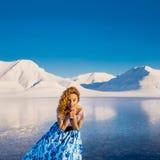 Girlbeautifulblonde in een blauwe de zomerkleding op een achtergrond van blauwe bergen svalbard op Spitsbergen CIT Stock Foto