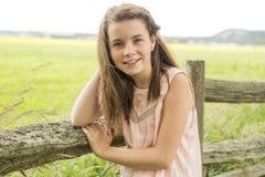 Girlclose adorabile ad un recinto il bello giorno di molla Bambino divertendosi all'aperto di estate Fotografia Stock
