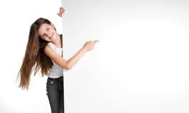 Girle al lado de un espacio en blanco blanco Fotos de archivo libres de regalías