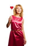 Girle blond retenant la coeur-forme rouge Photo libre de droits