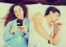 Girlfiend chatting on smartphone. While boyfriend is sleeping Royalty Free Stock Image