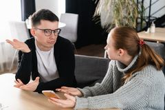 Girlfriend asking for explanation of her boyfriend sitting on a couch in the cafe stock photo
