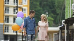 Girlfriend and boyfriend with balloons walking down street, stopping to kiss. Stock footage stock video
