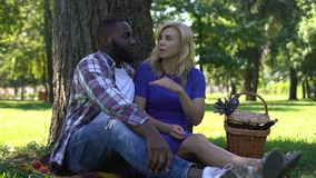 Girlfriend and boyfriend discussing relationship on picnic, biracial love, relax. Stock footage stock video