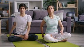 Girlfriend and boyfriend exercising at home then relaxing in lotus position. Siting on floor putting hands on knees resting enjoying peaceful atmosphere stock video