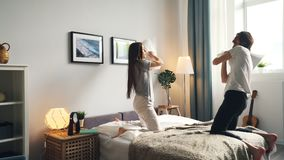 Girlfriend and boyfriend fighting pillows then kissing in bed at home. Girlfriend and boyfriend attractive young people are fighting pillows having fun then stock footage