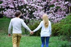 Girlfriend and boyfriend hold hands in spring park, back view. Love, romance, relations, family. Sensual women and men date in blossoming garden. Spring stock photos