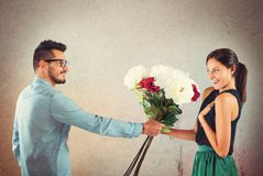 Girlfriend and boyfriend. Lover boy gives flowers to his girlfriend stock photo