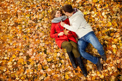 Girlfriend with boyfriend lying on fallen leaves in park Royalty Free Stock Photo