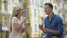 Girlfriend and boyfriend making soap bubbles and kissing, sweet relationship. Stock footage stock video footage