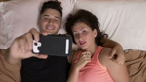 Girlfriend and boyfriend sitting in bed watching horror movie on internet using smartphone stock video