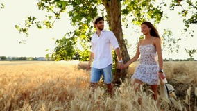 Girlfriend and boyfriend walking across a wheat field. Couple in love at sunset light in the middle of nature walking and relaxing surrounded by trees / slow-mo stock video footage