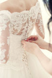 Girlfriend of the bride helps to dress a corset. The hand of the girlfriend clasps buttons on the bride's corset Stock Photography