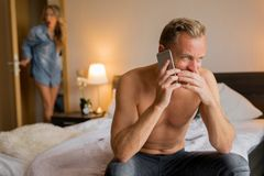Girlfriend caught her cheating boyfriend while he`s on phone with another woman. Cheating concept stock photo