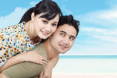 Girlfriend enjoying piggyback ride on beach. Girlfriend enjoying piggyback ride on boyfriend's at the beach royalty free stock photo