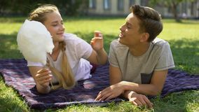 Girlfriend feeding boyfriend with cotton candy, leisure time, fooling around stock footage