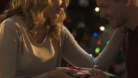 Girlfriend giving Christmas present and kissing boyfriend, pleasant surprise. Stock footage stock footage